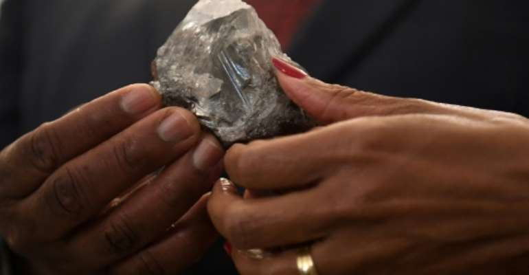 A member of the Botswana cabinet holds the 1,174-carat diamond in Gaborone on Wednesday.  By Monirul Bhuiyan (AFP)