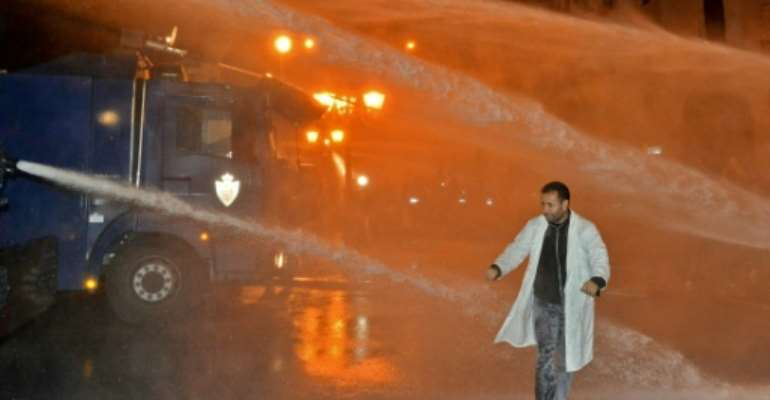 A Moroccan teacher walks through a water cannon during a demonstration calling for permanent contracts.  By - (AFP)