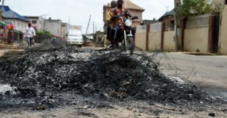 A motorcycle taxi in the district of Ojodu drives past the remains of a fire set to ward off gangs of robbers.  By PIUS UTOMI EKPEI (AFP)