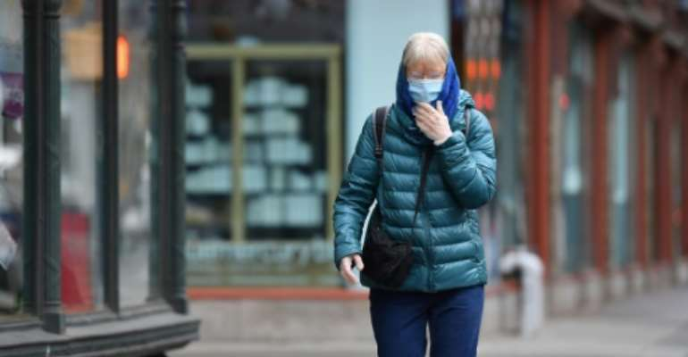 A New Yorker wears a face mask on the street.  By Angela Weiss (AFP)