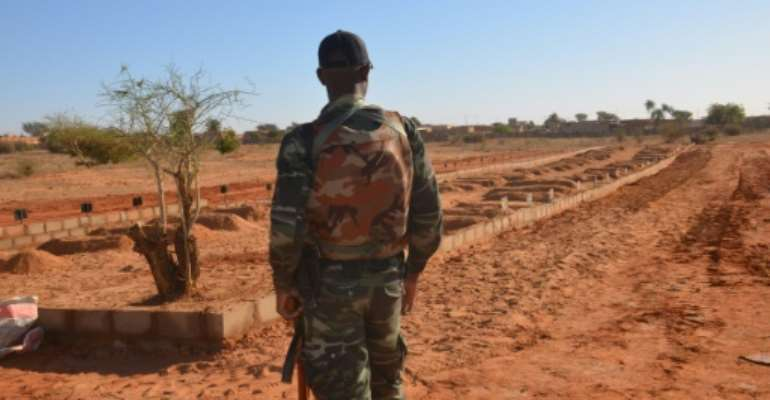 A Nigerien soldier looks at the graves of military personnel killed in a jihadist attack ahead of the arrival of G5 Sahel leaders on December 15, 2019.  By Boureima HAMA (AFP/File)