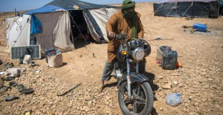 A Nomadic herder rides his motorcycle near tents in the southern Moroccan Tiznit province in the region of Souss-MassaDrought has turned parts of the plateaus of Tiznit arid, and when water becomes scarce, tensions rise.  By FADEL SENNA (AFP)