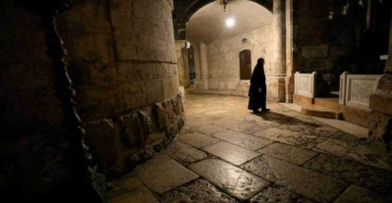 A nun walks along a deserted corridor in the Church of the Holy Sepulchre, believed by Christians to be the burial site of Jesus Christ.  By Emmanuel DUNAND (AFP)