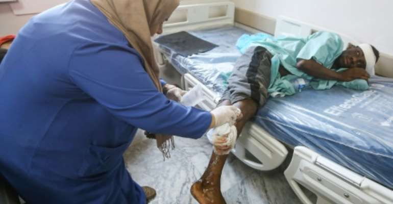 A nurse cleans the wound of a wounded migrant at a medical emergency ward in a Tripoli hospital on Wednesday.  By Mahmud TURKIA (AFP)