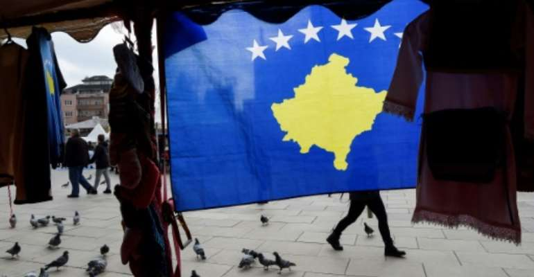 A pedestrian walks behind the Kosovo flag ahead of last year's 10th-anniversary celebrations in Pristina of Kosovo's declaration of independence.  By Armend NIMANI (AFP)