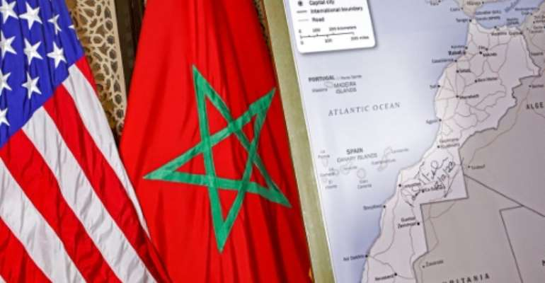 A photograph taken on December 12, 2020 shows  US and Moroccan flags next to a US State Department authorised map recognising the contested territory of Western Sahara as part of Morocco.  By - (AFP/File)