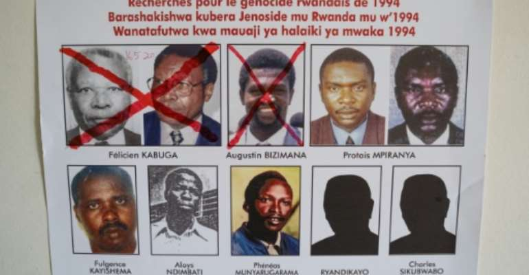 A picture taken on May 19, 2020, shows key suspects in the 1994 Rwandan genocide, on a wanted poster on the wall at the Genocide Fugitive Tracking Unit office in Kigali, Rwanda.  By Simon Wohlfahrt (AFP)