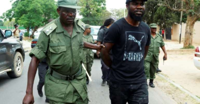 A police officer arrests Zambian musician Chama Fumba, known as as Pilato, in 2017.  By DAWOOD SALIM (AFP/File)
