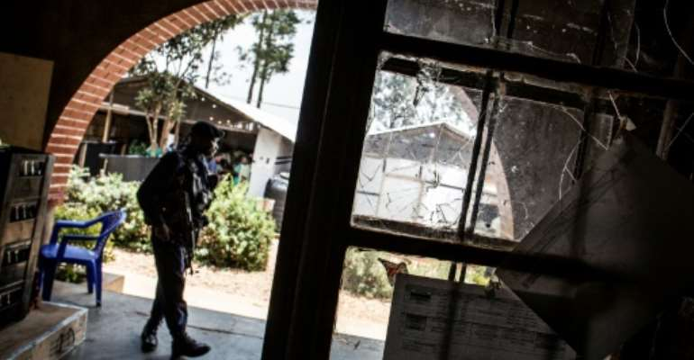 A police officer stands guard beside a window full of bullet holes at an Ebola treatment centre in Butembo.Suspected Mai-Mai tribal militia raided the ETC and killed a policeman and wounded a health worker early in March.  By JOHN WESSELS (AFP/File)