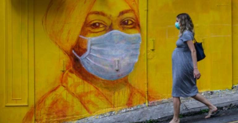 A pregnant woman wearing a face mask as a precautionary measure walks past a street mural in Hong Kong.  By ANTHONY WALLACE (AFP)