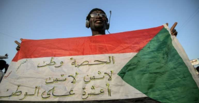 A protester flashes a Sudanese flag covered with patriotic slogans outside army headquarters in Khartoum.  By Mohamed el-Shahed (AFP)