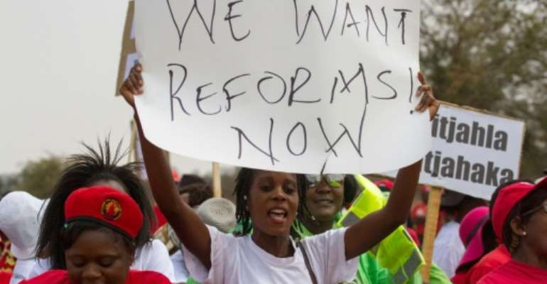 A protester holds a placard as Zimbabwe opposition supporters under the National Electoral Reform (NERA) coalition march through the streets of Bulawayo, on September 17, 2016.  By Zinyange Auntony (AFP)
