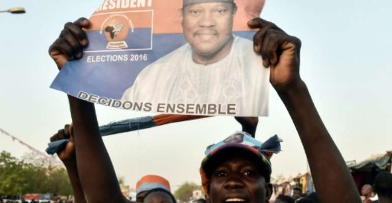 A protester holds up a flier of Niger opposition figure Hama Amadou, who turned himself in to police on Friday.  By ISSOUF SANOGO (AFP/File)