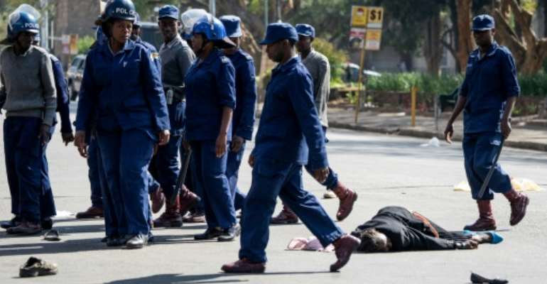 A protester lies on the ground after being beaten by police.  By Zinyange Auntony (AFP)
