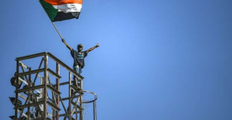 A protester waves a Sudanese flag on top of a tower during a sit-in outside the army headquarters in the capital Khartoum on April 30, 2019.  By OZAN KOSE (AFP)