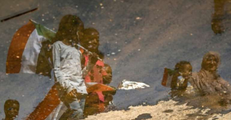 A reflection in a puddle of Sudanese protesters as they carry national flags outside the army headquarters in the capital Khartoum on Saturday.  By OZAN KOSE (AFP)