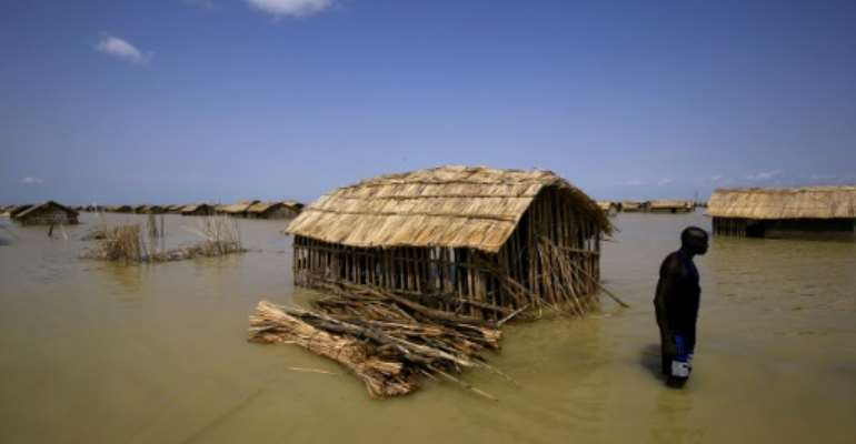 A South Sudanese refugee tries to repair his hut in flooded waters from the White Nile at a refugee camp which was inundated after heavy rain near in al-Qanaa, on September 14, 2021.  By ASHRAF SHAZLY (AFP/File)