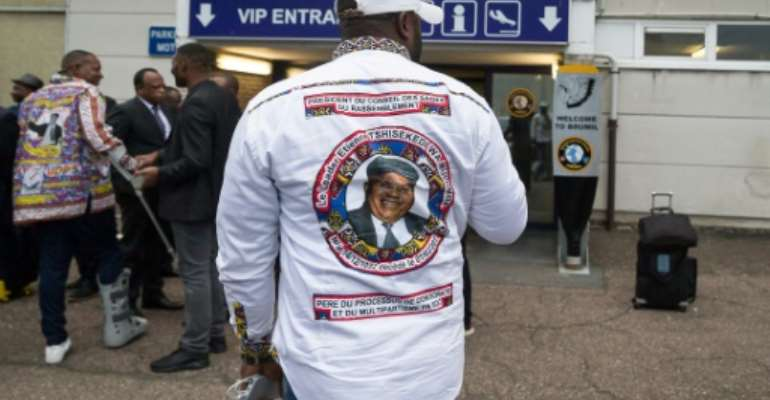 A stranded traveler, wearing a portrait of Etienne Tshisekedi on his shirt, stands outside the airport in Melsbroek after the flight for the repatriation of the remains of the late Congolese opposition leader was cancelled.  By JAMES ARTHUR GEKIERE (BELGA/AFP)