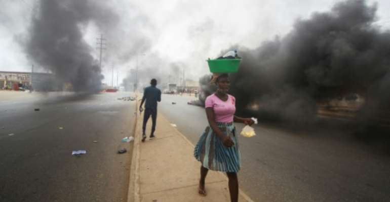 A street vendor walks past smoke from burning tyres during a anti-government demonstration in Luanda on October 24, 2020.  By Osvaldo Silva (AFP)