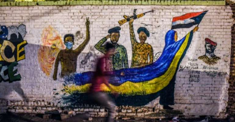A Sudanese protester runs past a mural during a demonstration near army headquarters in the capital Khartoum back in April.  By OZAN KOSE (AFP/File)