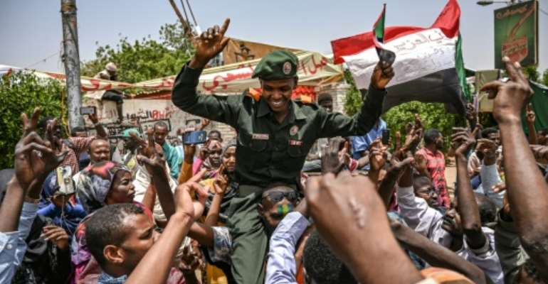 A Sudanese soldier joins protesters outside the army complex in Khartoum.  By OZAN KOSE (AFP)