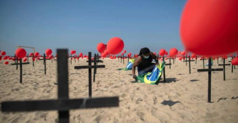 A thousand red balloons were released during a tribute to COVID-19 victims organized by an NGO at the Copacabana beach in Rio de Janeiro on August 08, 2020.  By Mauro Pimentel (AFP)