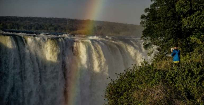 A tourist takes a photograph of the rainbow over Victoria Falls in Zimbabwe, where the number of tourists jumped by nearly 50 percent in the first quarter of tis year.  By Zinyange AUNTONY (AFP)