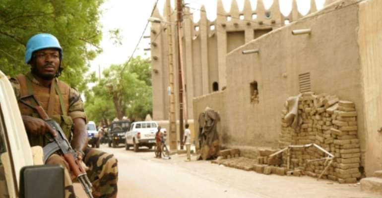 A UN peacekeeper patrols outside the mosque in Mopti, central Mali: two members of the peacekeeping mission have died of coronavirus, the organisation said.  By Sebastien Rieussec (AFP)