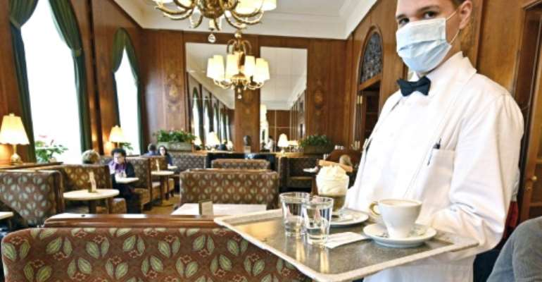 A waiter wearing a mask at a newly reopened cafe in Vienna, as Austria lifts its coronavirus lockdown.  By HANS PUNZ (APA/AFP)
