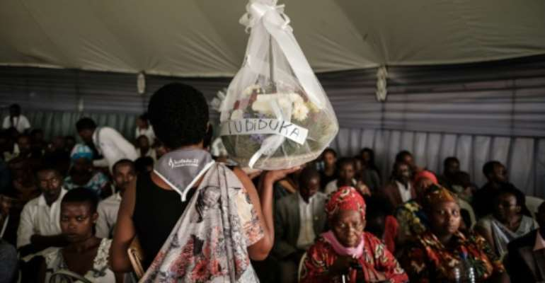 A woman carries flowers to offer before the mass funeral to bury 81 coffins containing newly discoverd remains of 84,437 victims of the 1994 genocide in the mass grave at the Nyanza Genocide Memorial, suburb of the capital Kigali, on May 4, 2019. The remains of nearly 85,000 people murdered in Rwanda's genocide were laid to rest on May 4 in a sombre ceremony in Kigali, a quarter of a century after the slaughter.  By Yasuyoshi CHIBA (AFP)