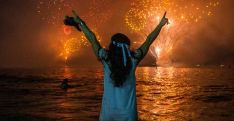 A woman celebrates as she watches the traditional New Year's fireworks at Copacabana Beach in Rio de Janeiro, Brazil, with an estimated three million revelers.  By DANIEL RAMALHO (AFP)