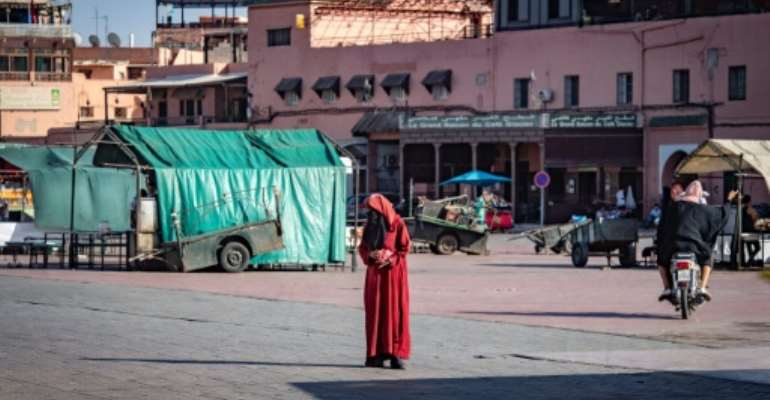 A woman crosses the legendary Jemaa el-Fna square in the Moroccan city of Marrakesh, currently empty of its usual crowds due to the Covid-19 pandemic.  By FADEL SENNA (AFP/File)