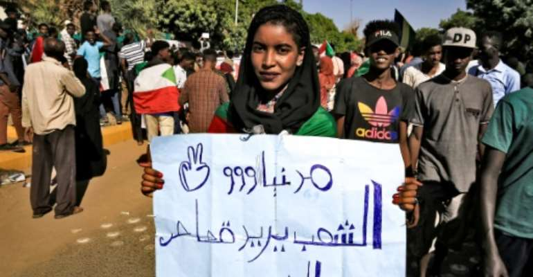 A woman holds up a sign reading in Arabic: