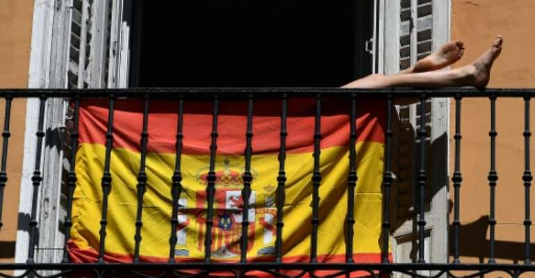 A woman sunbathes behind a Spanish flag on her balcony in Madrid during the national lockdown.  By Gabriel BOUYS (AFP)