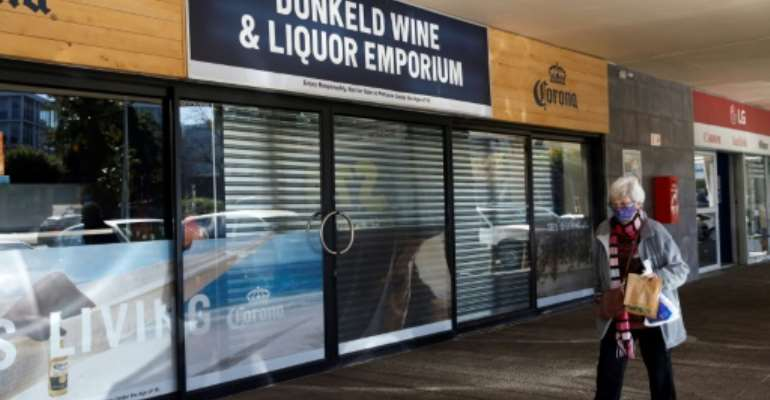 A woman walks past a closed liquor shop in Johannesburg in July 2020.  By Michele Spatari (AFP/File)