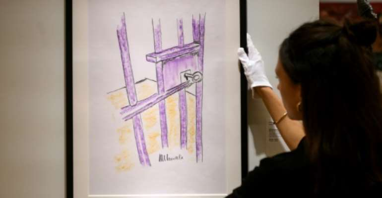 A worker at Bonhams auction house holds a sketch by Nelson Mandela --