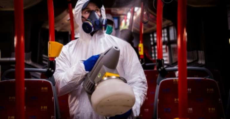 A worker disinfects the  interior of a public bus in the capital of Slovakia.  By VLADIMIR SIMICEK (AFP/File)