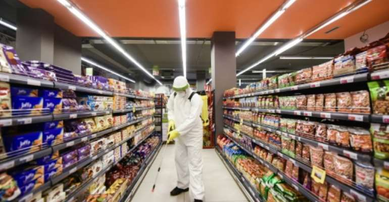 A worker disinfects the floor of a supermarket in Kosovo.  By Armend NIMANI (AFP)