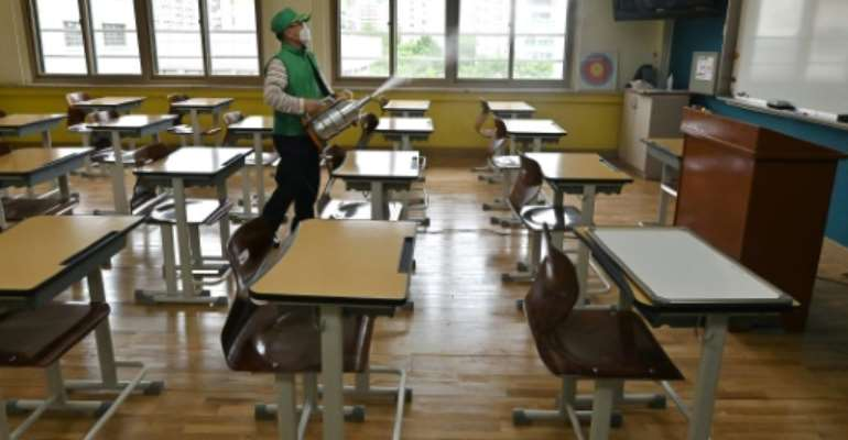 A worker sprays disinfectant in a classroom at a high school in Seoul.  By Jung Yeon-je (AFP)