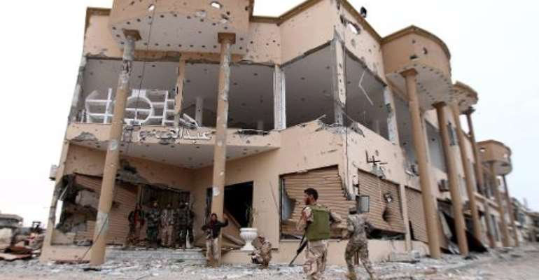 Fighters loyal to Khalifa Haftar, a retired general and former chief of staff for Moamer Kadhafi, fighting alongside Libyan army troops, stand at the entrance of a destroyed building in Benghazi on December 16, 2014.  By Abdullah Doma (AFP)
