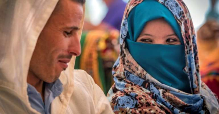A young Amazigh couple smile at each other as they wait for their turn at a group wedding in Morocco's Atlas mountains.  By FADEL SENNA (AFP)