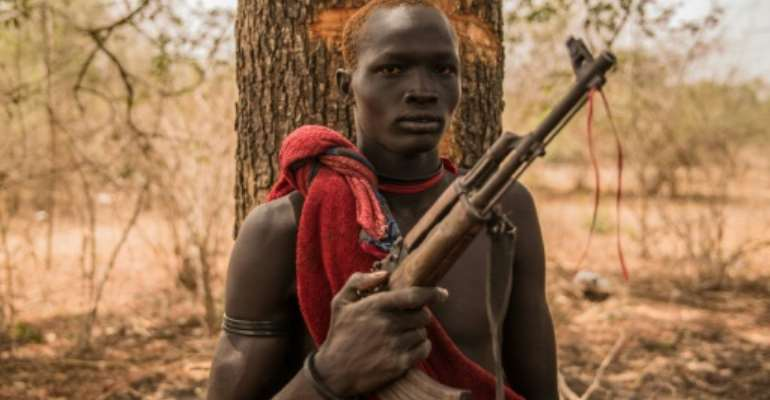 A young herdsman from the Dinka tribe poses with a semi-automatic weapon. Guns are rife in rural South Sudan, for self-protection or defence against cattle raiders.  By Stefanie GLINSKI (AFP)