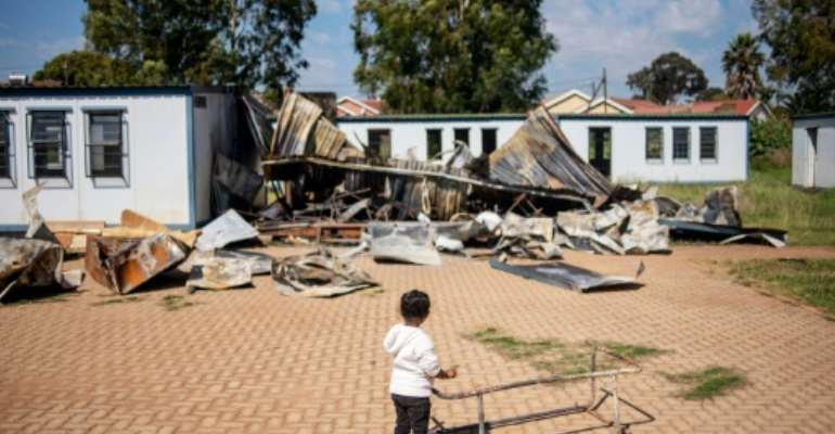 A young member of the 'Coloured' community stands in the courtyard of Oakdale Secondary School in Eldorado Park, on the outskirts of Johannesburg. Several classrooms were destroyed during a student strike in April.  By Michele Spatari (AFP)
