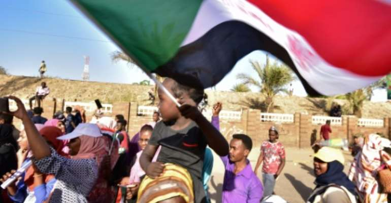 A young Sudanese boy waves a national flag as people celebrate concessions by Sudan's new military ruler, in Khartoum, on Saturday.  By AHMED MUSTAFA (AFP)