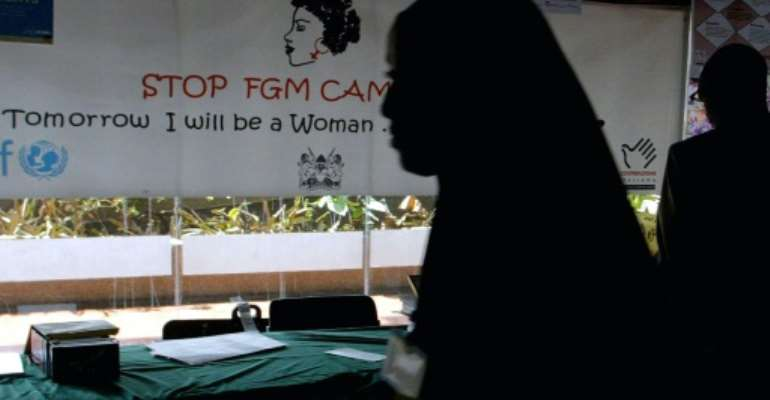 A young woman walks past a banner against female genital mutilation.  By SIMON MAINA (AFP/File)