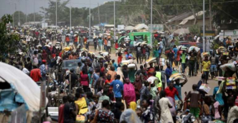 Abuja residents carry off sacks of supplies meant for distribution during coronavirus lockdowns as authorities struggle to halt the pillaging.  By Kola Sulaimon (AFP)