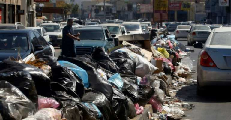 Across Libya's capitol Tripoli, tonnes of waste overflows from bins and piles up on roadsides.  By Mahmud TURKIA (AFP)