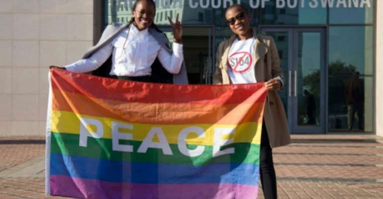 Activists pose with a rainbow flag as they celebrate the Botswana High Court's decision to decriminalize same-sex relationships.  By Tshekiso Tebalo (AFP/File)