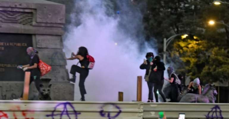 Activists vandalise a monument in Mexico City.  By PEDRO PARDO (AFP)