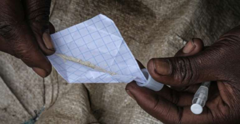 Addiction: A heroin user in Nairobi's Kawangware slum prepares a fix.  By Yasuyoshi CHIBA (AFP)